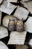 Hand-made, needle-felted, woollen owls on stacked firewood