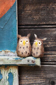 Two hand-made, felted, woollen owls against wooden background