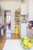 Basket of lemons and limes in kitchen furnished with individual pieces