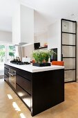 Large island counter with black cabinets and white worksurface