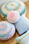 Various pastel cushions with crocheted covers made from T-shirt yarn