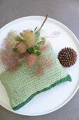 Grünes gehäkeltes Kissen aus T-Shirtgarn auf rundem Couchtisch