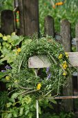 Wreath of wildflowers on backrest of vintage garden chair in front of weathered picket fence