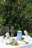 Set garden table decorate with posy of colourful wildflowers and pale blue enamel coffee pot