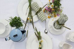 Table set with posy of colourful wildflowers and arranged napkins