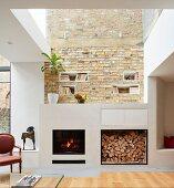 Offener Kamin und Brennholzlager in Loftwohnung mit Ziegelwand