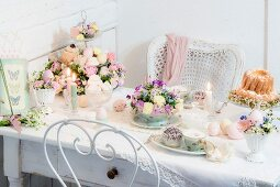 Easter table romantically set with delicate flowers and lit candles