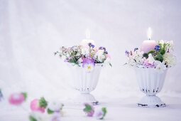 Romantic flower arrangement and lit candle