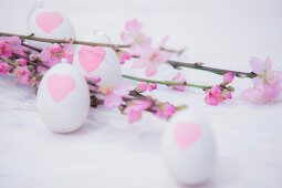 Pink-flowering branches and white eggs painted with hearts