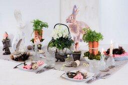 Festlich gedeckter Ostertisch mit dekorativen Gestecken und Hasenfiguren