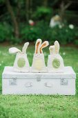 Hand-made bunnies on vintage suitcase in garden