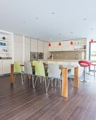 Modern dining table and colourful chairs in open-plan kitchen