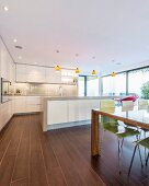 Dining table and wood-effect tiles in open-plan kitchen
