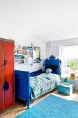 Blau gestrichenes antikes Bett im Kinderzimmer mit blauem Teppich