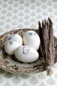 Eggs stamped with lettering next to bundle of feathers on plate