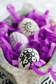 Decorated Easter eggs and purple paper strips with zigzag edges in stone bowl