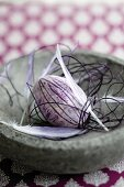 Easter egg painted purple, feathers and delicate cord in stone dish