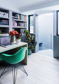Study room with bookcase, desk and green shell chair