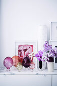 Colorful glass decoration and orchids on lowboard