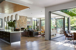 Open living room with window fronts to the garden and terrace