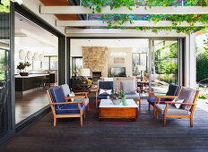 Upholstered wooden armchairs under the overgrown pergola