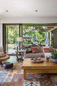 Living room in natural tones with an open glass front to the garden