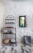 Ornate metal shelves next to small window in plastered stone wall