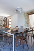 Various chairs around dining table in front of doorway in stone wall
