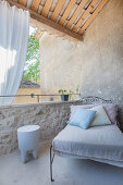 Old metal bed used as couch with scatter cushions on Mediterranean roof terrace