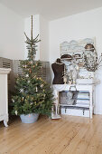 Christmas tree in zinc tub next to arrangement of vintage items