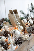 Silver Christmas tree baubles, pine cones and fairy lights in wooden crate