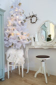 Christmas tree decorated with vintage photos next to dressing table