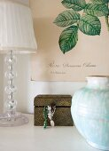 Vase, lamp and jewellery box below botanical illustration on poster