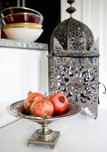 Pomegranates in silver dish in front of Oriental lantern