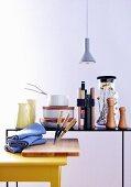 Gelber Küchentisch mit Küchenbrett und Messern vor filigranem Metalltisch mit Küchenutensilien und Büchern