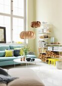 Gemütlicher hoher Wohnbereich mit Polstermöbeln, Couchtisch und Holzscheiten in weissem Regal