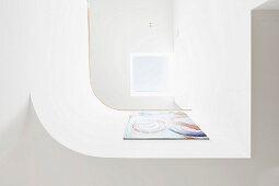 Blick auf gerundete, weisse Brüstung mit Gemälde und hellem Oberlichtfenster
