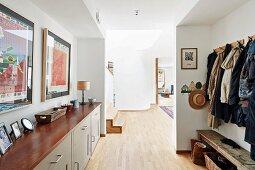 Garderobenbereich mit Sideboard und Wandgarderobenleiste, Blick in offenen, hellen Wohnbereich