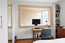 Home Office mit Computerbildschrim in holzverkleideter, abgeschrägter Fensterlaibung