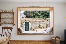 Gemütliche Leseecke in gepolsterter Panorama-Fensterlaibung mit Blick auf traditionelle Gartenmauer