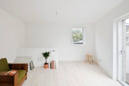 Helles Dachgeschosszimmer mit weißem Dielenboden und grünem Vintage Sessel