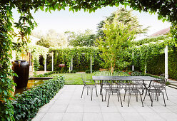 Terrace area with table and chairs made of metal, surrounded by green plants and lawn