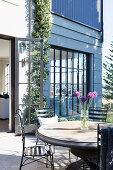 Runder Gartentisch mit schwarzen Stühlen auf der Terrasse