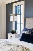 Würfelförmige Hängeleuchte mit goldenem Rahmen am Bett
