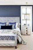 Elegantes Schlafzimmer mit grauem Polsterbett mit Polsterbank