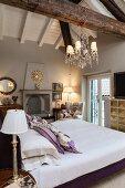 Bed with purple frame below exposed roof beams in bedroom