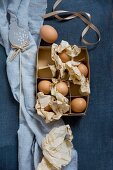 Eggs and crumpled paper in vintage cardboard box