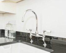 Spülenarmatur auf glänzender, schwarzer Granitküchenarbeitsplatte