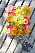 Posies of garden flowers next to vintage cutlery on weathered garden table