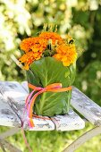 Tagetes wrapped in green leaves and ribbon